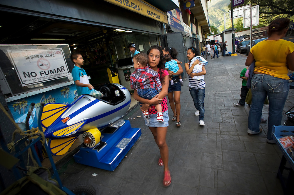 Keisy Acevedo, 17, walks to buy diapers through a slum in Caracas, Venezuela.  Acevedo got pregnant with her 9-month old son John, when she was 15 years old.