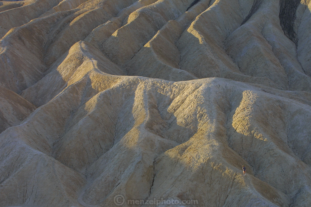 A runner, bottom right, takes an early morning run on eroded hills. Seen from Zabriskie Point, Death Valley, CA. Christmas road trip from Napa, California to Sedona, Arizona and back.