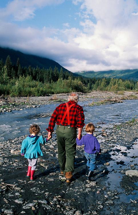 Alaska. Girdwood. Sourdough Grandfather helps his grandchildren across the stream.