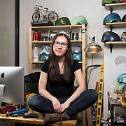 """February 24, 2014 - New York, NY : <br /> Danielle Baskin, founder of Belle Helmets, poses for a portrait in her office/studio space at 115 E. 23rd Street in Manhattan on Monday afternoon, Feb. 24. Danielle hand-paints bicycle helmets, which she sells to clients in New York and across the globe. Her setup includes a 21.5"""" iMac, visible at left, and an iPhone 5S, in foreground at center left in an OtterBox case.  <br /> CREDIT: Karsten Moran for Macworld Magazin"""