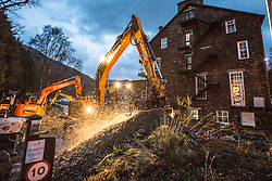 © Licensed to London News Pictures. 11/12/2015. Glenridding UK. Rescue services & volunteers are franticly working into the night to try & clear the beck that flooded the village twice this week and reenforce defences tonight with the threat of more heavy rain & snow. Photo credit: Andrew McCaren/LNP