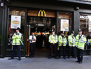Police and staff stand outside a McDonals's restaurant as demonstrators pass during the Time To Act, National Climate March organised by Campaign Against Climate Change in London, England on March 7, 2015