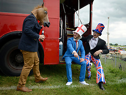 © Licensed to London News Pictures. 01/06/2012. Epsom , UK Finn Grant (pointing) and Robin Voogd sit on the back of a double decker bus wearing union flag outfits whilst talking to David Goddard who is wearing a horse mask. . Ladies Day today 1st June 2012 at Epsom 2012 Investic Derby Festival. The Queen will attend tomorrow's race meet as part of the 60th Jubilee celebrations. Photo credit : Stephen Simpson/LNP