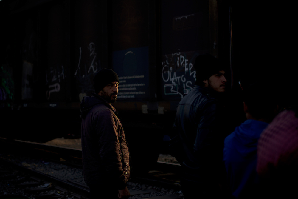 Migrants and refugees await, under police guard, to pass the trains tracks near the border between Greece and Macedonia in Idomeni, Greece. Around 13,000 migrants and refugees, mostly from the Middle East and African nations, are believe to be stranded here awaiting a chance to proceed their journey towards Germany and other northern European countries.