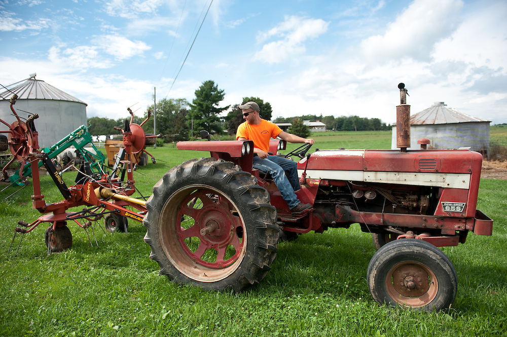 Man operating an antique tractor on a farm