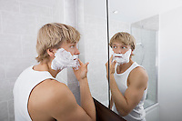 Mid-adult man applying shaving cream in bathroom