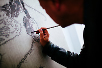 Artist Ye Yongqing at work on a new painting in the studio of his home in Dali City, China