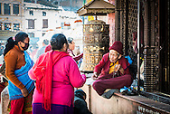 A monk accepts offerings at the Boudhanath stupa in Kathmandu, Nepal.