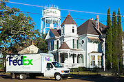 American scene - water tower and FedEx truck by a typical mansion house in Natchez, Mississippi, USA
