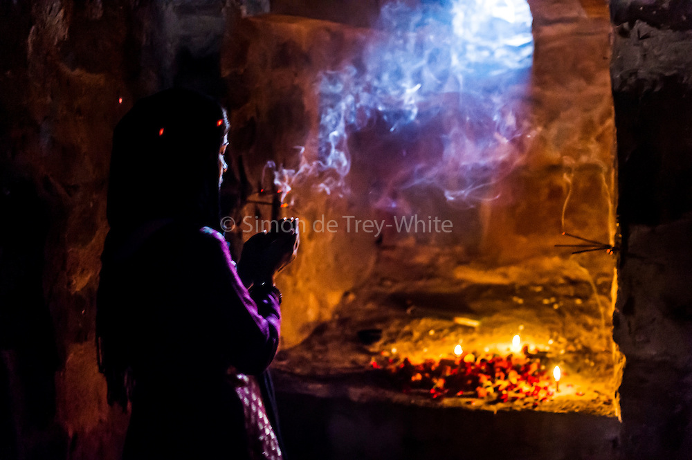 19th November 2015, New Delhi, India.  A woman prays at a shrine dedicated to Djinn worship in the ruins of Feroz Shah Kotla in New Delhi, India on the 19th November 2015<br /> <br /> PHOTOGRAPH BY AND COPYRIGHT OF SIMON DE TREY-WHITE a photographer in delhi<br /> + 91 98103 99809. Email: simon@simondetreywhite.com<br /> <br /> People have been coming to Firoz Shah Kotla to pray to and leave written notes and offerings for Djinns in the hopes of getting wishes granted since the late 1970's. Jinn, jann or djinn are supernatural creatures in Islamic mythology as well as pre-Islamic Arabian mythology. They are mentioned frequently in the Quran  and other Islamic texts and inhabit an unseen world called Djinnestan. In Islamic theology jinn are said to be creatures with free will, made from smokeless fire by Allah as humans were made of clay, among other things. According to the Quran, jinn have free will, and Iblīs abused this freedom in front of Allah by refusing to bow to Adam when Allah ordered angels and jinn to do so. For disobeying Allah, Iblīs was expelled from Paradise and called &quot;Shayṭān&quot; (Satan).They are usually invisible to humans, but humans do appear clearly to jinn, as they can possess them. Like humans, jinn will also be judged on the Day of Judgment and will be sent to Paradise or Hell according to their deeds. Feroz Shah Tughlaq (r. 1351&ndash;88), the Sultan of Delhi, established the fortified city of Ferozabad in 1354, as the new capital of the Delhi Sultanate, and included in it the site of the present Feroz Shah Kotla. Kotla literally means fortress or citadel.