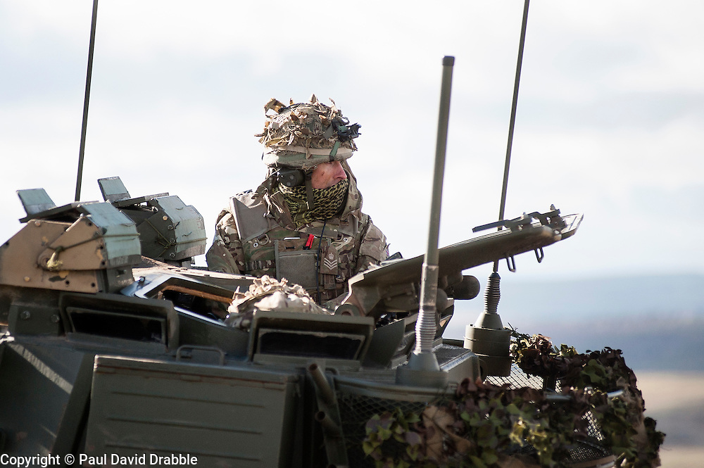 A sergeant of the 19 Regiment Royal Artillery (The Scottish Gunners) observes from the turret of his Warrior  the accuracy of live rounds landing down range during exercise Steel Sabre. A large Scale military live fire exercise on Otterburn Training Area it involves 1400 troops the majority from the Royal Artillery 1st Artillery Brigade and brings all the components of an effective Artillery group together to train in delivering firepower on the battlefield.<br /> <br />   02 March 2017 <br />   Copyright Paul David Drabble<br />   www.pauldaviddrabble.co.uk