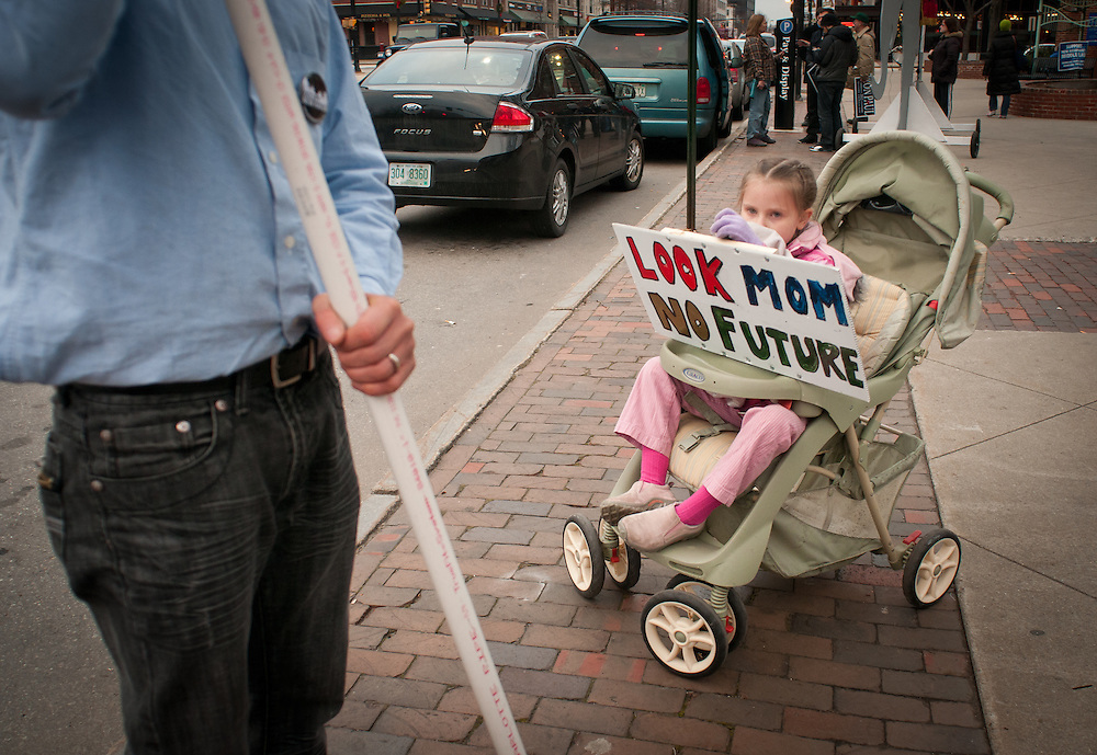Dan Garrett and his daughter Abigail, 6 of Hamden Conn. takes part in Occupy NH's rally as part of the Occupy the Primary protest in Manchester, NH.