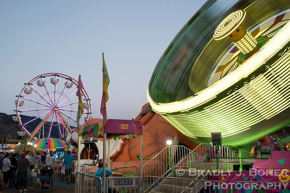Carnival rides spin into the night at dusk Saturday at the Teton County Fair.