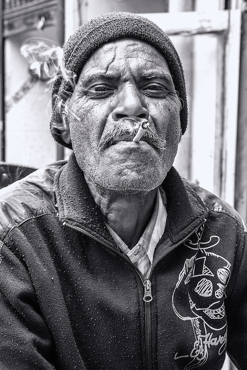 Black and white Portrait of an adult smoking in New Delhi