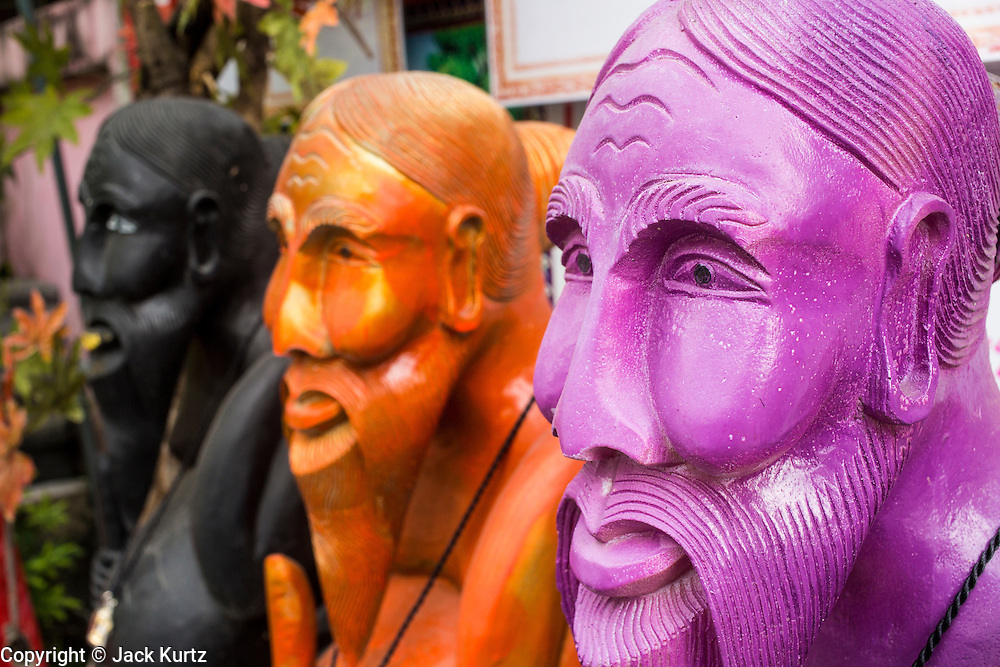 """03 MARCH 2013 - BANGKOK, THAILAND:  Statues of Chuchok in the Chuchok shrine. The Chuchok Shrine is in suburban Bangkok. More than 100 people a week come to the shrine to pray for good fortune or good health. People whose prayers are answered return to the shrine with """"coyote dancers"""" to make merit and thank Chuchok. Coyote dancing is a Thai phenomenon created after the US movie """"Coyote Ugly"""" where attractive young women dance in a sexually suggestive way, usually for pay. They're common at bars and festivals. Coyote dancers are typically better paid than other Thai women in the hospitality industry and usually are not allowed to date or see customers are off the dance floor. Coyote dancers perform at the Chuchok shrine because according to Buddhist literature Chuchok was a relatively repulsive old hermit and Brahmin priest who was cared for by a young woman after he made her family's wishes come true.  PHOTO BY JACK KURTZ"""