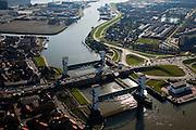 Nederland, Zuid-Holland, Capelle aan den IJssel, 20-03-2009; stormvloedkering in de Hollandsche IJssel. Bij storm en dreigend hoog water wordt een van de twee schuiven naar beneden gelaten, de tweede schuif dient al reserve. De scheepvaart kan de gesloten kering paseren via de naastgelegen schutsluis. Linksboven het eiland Stormpolder (Krimpen aan den IJssel). De stormvloedkering maakt deel uit van de Deltawerken en is als eerste voltooid in 1958. Ten tijde van De Ramp - watersnood 1953 - werd het zeewater door de storm opgestuwd en dreigde de verzwakte rivierdijken in het achterland het te begeven waardoor grote van het laag gelegen westen van Nederland ondergelopen zouden zijn..Netherlands, Capelle at the river IJssel, near Rotterdam: storm surge barrier, protects the highly populated western part of Holland, which lies below sea level. In case of storm and threat of high water, one of the two doors is lowered into the river (the second door is a spare one). The lock next to the barrier allows shipping when the barrier is closed.Swart collectie, luchtfoto (toeslag); Swart Collection, aerial photo (additional fee required).foto Siebe Swart / photo Siebe Swart