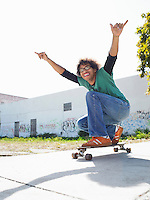 Young man with arms raised on skateboard outdoors portrait