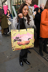 © London News Pictures. 17/11/2011. London, UK. A shopper shows of her purchase at the Launch of the new Versace collection at H&M on Regent Street, London today (17/11/2011). Shoppers had queued for nearly 24 hours to be first in line for Versace's hotly anticipated collection : Ben Cawthra/LNP