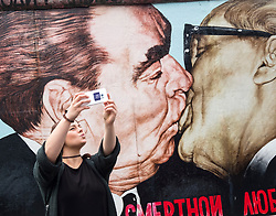 Tourist taking selfie photo of mural painted on original section of Berlin Wall at East Side gallery in Berlin, Germany ...Editorial Use Only