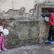Quasi 800 profughi di cui più di 100 bambini vengono ospitati nella struttura di accoglienza Baobab di Via Cupa a Roma. La struttura può accogliere circa 220 migranti. Semplici cittadini e il gruppo SEL hanno raccolto generi alimentari da distribuire agli all'interno della struttura. Due bambini sul marciapiede fuori dal centro giocano con i palloncini.