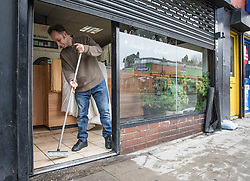 © Licensed to London News Pictures. 27/11/2016. London, UK. Mr Erkanzeki, owner of Lewisham Dry Cleaners on Lee High Road, sweeps water from inside his shop after a tourist coach fell into a sinkhole caused by a burst water mains. The road has been closed off and police declared a 'major incident' after a French tourist coach with 100 passengers on board fell into a sinkhole caused by a burst water mains, flooding a long stretch of the road including many local businesses. . Photo credit: Rob Pinney/LNP