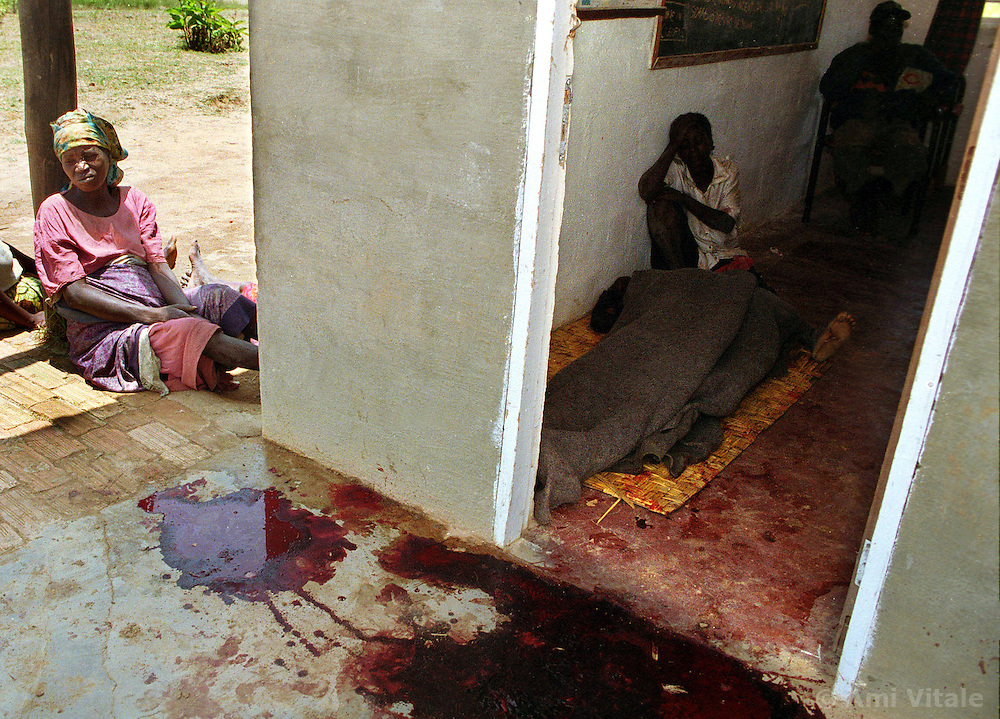 Family members of a child and guard who were killed during a late night looting of an orphanage sit next to the blood spattered entrance way to the school in Huambo, Angola. It is a common scene in Angola's brutal 26 year-civil which has displaced around two million people - about a sixth of the population - and 200 die each day according to United Nations estimates. (photo by Ami Vitale)