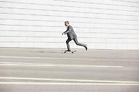 Side view of businessman skateboarding on street