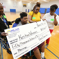 Keshun Vasser, 12, of Tupelo, gets ready for a picture with his great grandmother Ellen Boggan, Teetta Vasser, his mother and Natasha Pack, his cousin, as he holds a $50,000 check he and his family received Wednesday morning at Tupelo Middle School. Keshun was shot in the neck in September and is paralyzed from the waist down and after various fundraisres through the schools and his church, West Jackson Street Baptist Church, he will now be able to purchase a wheelchir accessible van.