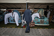A man carrying a case bearing the Union Jack looks at mechanics carry out work on their vintage vehicles at the Goodwood Revival in Chichester, England   Friday, Sept. 9, 2016 The historic motor racing festival celebrates the mid-20th-century golden era of the racing circuit and recreates the atmosphere from the 1950s and 1960s.(Elizabeth Dalziel)