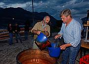 "Fabrication du ""vin cuit"" sur feu ouvert à Lessoc. Durant plusieurs jours et nuits le jus de pommes et de poires est cuit sur feu ouvert. Lors de la mise en bouteille du préciux jus, les habitants se rassemblent pour fêter dignement cet évenement. Fête populaire du Vin Cuit 2007 à Lessoc. <br /> Herstellung des ""Vin cuit"" auf offenem Feuer in Lessoc, Greyerz. Die Saft von frisch gepressten Äpfeln und Birnen wird während mehreren Tagen und Nächten auf offenem Feuer eingekocht und anschliessend abgefüllt. © Romano P. Riedo | fotopunkt.ch"