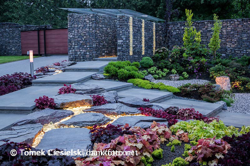 Modern garden after sunset. Light stripes located under the rocks. Design: Lukasz Kilarski