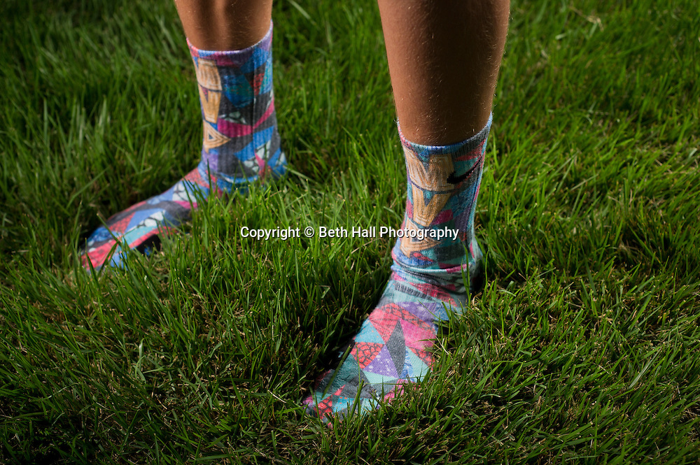 "Winston Robson, 15, of Bentonville, Ark., shows a pair of his sock made by Rock ""Em Apparel while walking through his yard on Tuesday, Sept. 10, 2013, in Bentonville, Ark. Robson owns several pair of the custom Nike Elite socks. Photo by Beth Hall"