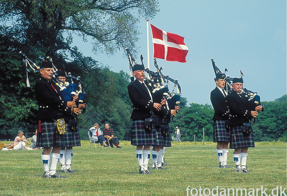 Bagpipers in front of the Danish flag at Knuthenborg