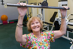 Women using lat pull down equipment in a YMCA gym,