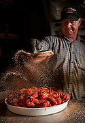 Donni Choate sprinkles his seasoning mix onto a tray of boiled crawfish at Cajun Claws in Abbeville, Louisiana.
