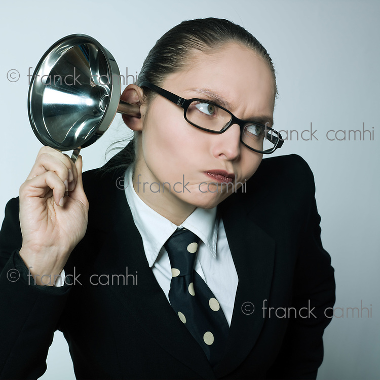 studio shot portrait of a beautiful curious business woman in a costume suit hearing aid funnel curious spying gossip