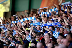 Huddersfield Town fans in the stands show their support by holding up scarves during the match