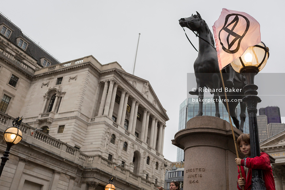 A young environmental activist protests about Climate Change beneath the statue of the Duke of Wellington during the blockade at the junction at Bank outside the Bank of England in the heart of the capital's financial district, the City of London aka the Square Mile, on the seventh day of a two-week prolonged worldwide protest by members of Extinction Rebellion, on 14th October 2019, in London, England.