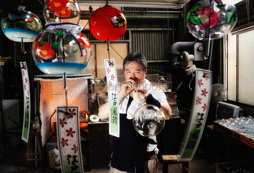 """Yutaka Shinohara blows traditional wind chimes, known as """"Edo furin,"""" at his workshop at Shinohara Furin Honpo in Tokyo, Japan. The craft dates back over 200 years in Japan, and is a common sound in the summer, thought to bring mental coolness on a steamy hot summer's day."""