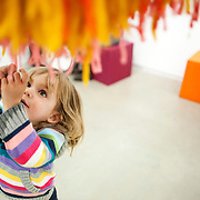 "March 10, 2012 - New York, NY : Natalie Retterath, 2, plays beneath a hanging yarn puppet created by Misaki Kawai -- part of Kawai's installation ""Love from Mt. Pom Pom"" -- at the Children's Museum of the Arts in the south village on March 10. CREDIT: Karsten Moran for The New York Times"