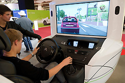 Visitors using Citroen fuel efficiency driving simulator at Paris Motor Show 2010