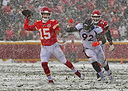 Quarterback Patrick Mahomes #15 of the Kansas City Chiefs throws a pass, scrambling through the snow, against defensive end Jonathan Harris #92 of the Denver Broncos during the second half at Arrowhead Stadium on December 15, 2019 in Kansas City, Missouri.