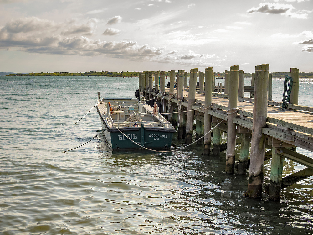 Wooden boat tied up to a pier. Peaceful scenic image. Woods Hole, Cape Cod MA.