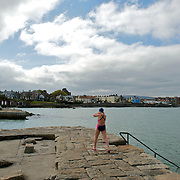 A woman prepares to jump into the sea at the Forty Foot bathing pools in Dun Laoghaire area, Dublin.