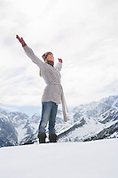 Woman standing on mountain peak with arms outstretched side view