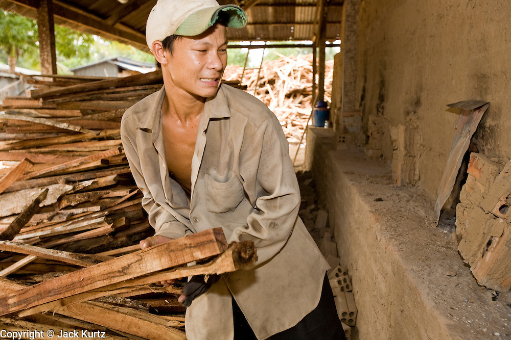30 JUNE 2006 - PHNOM PENH, CAMBODIA: A brick factory worker stuffs firewood into a kiln at a brick factory in Phnom Penh, Cambodia. This factory uses wood from rubber trees bought from Cambodian rubber plantations. According the United Nations Food and Agricultural Organization, there are more than 70 brick factories in Phnom Penh and its environs. Environmentalists are concerned that the factories, most of which burn wood in their kilns, contribute to deforestation in Cambodia. They are encouraging factory owners to switch to burning rice husks, as brick kilns in neighboring Vietnam do. The brick factories are kept busy feeding Phnom Penh's nearly insatiable appetite for building materials as the city is in the midst of a building boom brought by on economic development and the need for new office complexes and tourist hotels.   Photo by Jack Kurtz / ZUMA Press