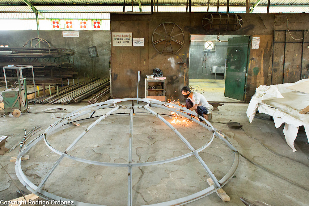 An employee wields a dome that will hold stained glass at the Eztu Glass factory in Tangerang, near Jakarta, Indonesia, on July 2, 2015.