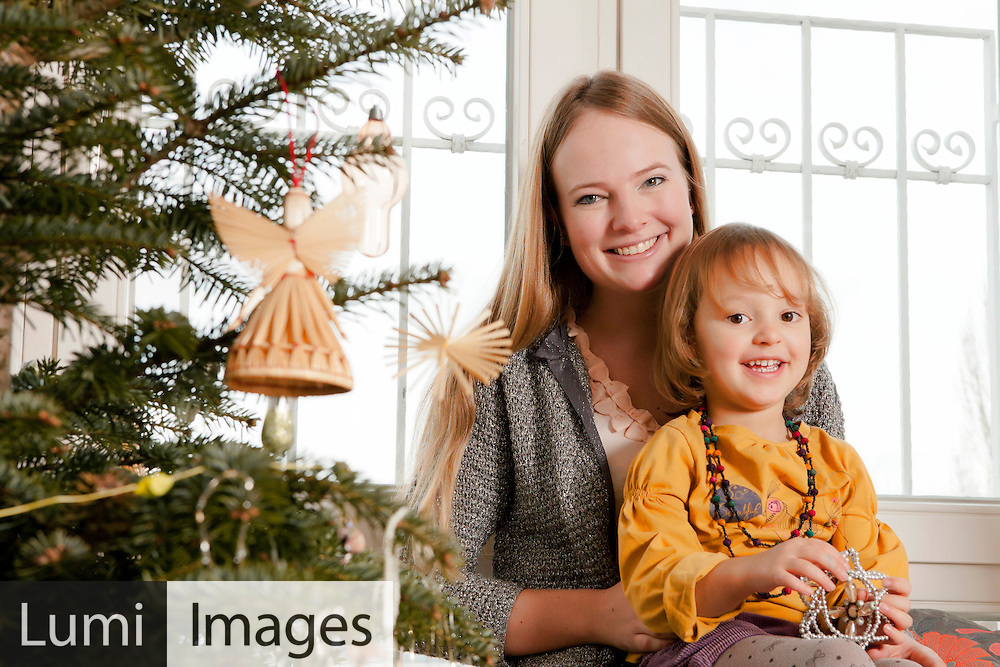 Mother and daughter decorating Christmas tree, Munich, Bavaria, Germany
