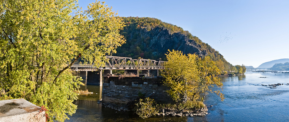 The Baltimore and Ohio Railroad Crossings are a set of railroad bridges (on the National Register of Historic Places) that span the Potomac River between Maryland Heights, Maryland and Harpers Ferry, West Virginia, USA. Two bridges comprise the current crossing. The older bridge (shown), a steel Pratt truss and plate girder bridge dating to 1894, carrying the B&O Valley line toward Winchester, Virginia along the Shenandoah River. A tunnel was built at the same time as the 1894 bridge to carry the tracks through Maryland Heights and to eliminate a sharp curve. The western end of the tunnel was widened in conjunction with the construction of the second bridge to allow the broadest possible curve across the river. Just downstream of the 1894 bridge, almost at the confluence of the Potomac and Shenandoah Rivers, are the ruins of two previous bridges on the same alignment. The newer of the bridges was a Bollman truss bridge that carried rail and highway traffic from 1870 until 1936, when it was swept away by a flood. As of 2008, Amtrak, the US national passenger rail system, provides service to Harpers Ferry twice a day (once in each direction). It is also served by the MARC commuter rail service, on its Brunswick line. The city's passenger rail station is located at the West Virginia end of the historic railroad bridge across the Potomac River. In addition about forty or fifty CSX freight trains daily pass through Harpers Ferry and over the bridge. Panorama stitched from 3 overlapping photos.