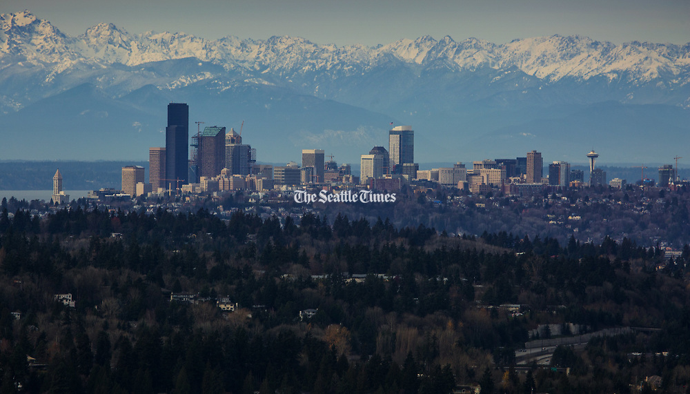 Snow on the Olympic mountain range can be seen behind the Seattle skyline.  Shot from Bellevue's Somerset neighborhood. (Ellen M. Banner / The Seattle Times)